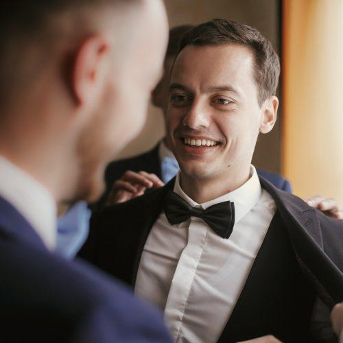 Groom getting ready in the morning with groomsmen in the room
